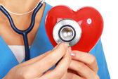 Doctor con estetoscopio examinando corazón rojo — Foto de Stock