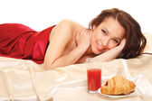 Girl lying on a bed with a served breakfast — Stock Photo