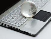 Crystal-glass globe on keyboard of modern notebook. — Stock Photo