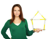 Woman holding a ruler in the form of a house. — Stock Photo