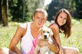 Casal com seu filhote de cachorro. — Fotografia Stock
