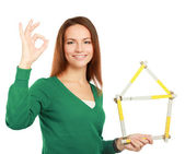 Woman holding a ruler in the form of a house and showing ok. — Stock Photo