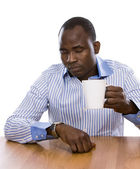 African man with cup of tea, sitting on the desk. — Foto de Stock