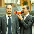 Two businessmen, one with a loudspeaker screaming — Stock Photo #43175277
