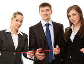 Businesspeople cutting a red ribbon — Stock Photo