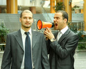 Two businessmen, one with a loudspeaker screaming — Stock Photo