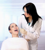 Female patient takes a dental attendance — Stock Photo