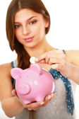 Woman standing with piggy bank — Стоковое фото