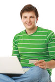 Man with  laptop, holding a credit card — Stock Photo
