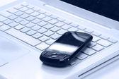 Telefon komórkowy na klawiaturze laptopa — Zdjęcie stockowe