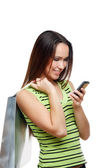 Girl calling by mobile phone with shopping bags — Stock Photo