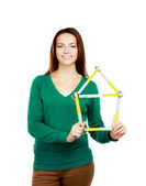 Woman holding a ruler in the form of a house — Stock Photo