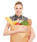 Woman in apron holding grocery bag — Stock Photo