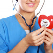 Doctor with stethoscope examining red heart — Stock Photo