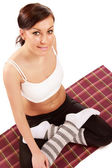 Young sportive girl sitting on the floor — Stock Photo