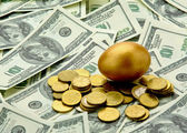 Gold egg lying on dollars — Stock Photo