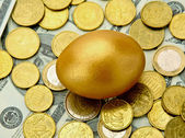 Gold egg lying on dollars and coins — Stock Photo