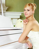 Beautiful, elegant bride by the piano. — Stock Photo