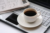 Cup of fragrant coffee on a morning paper — Stock Photo