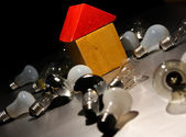 Light bulb and toy house. — Stock Photo