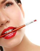 Woman's lips holding make up brush — Stock Photo