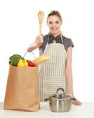 Woman in apron with grocery bag — Stock Photo