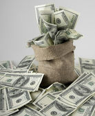 Canvas money sack with one hundred dollar bills — Stock Photo