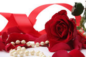 Pearl beads and red roses petals — Stock Photo