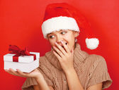 Woman on santa hat with christmas gift — Stock Photo