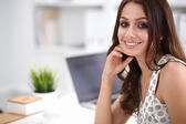 Attractive businesswoman sitting  on desk in the office — Photo