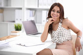 Attractive businesswoman sitting  on desk in the office — Stock fotografie