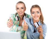 Two young women sitting with laptop  and credit cart showing ok — Stock Photo