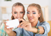 Two girls taking pictures on the phone at home — 图库照片