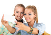 Two girls taking pictures on the phone at home — Stockfoto