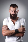 Portrait of handsome bearded man standing with crossed arms, isolated on grey background — Foto Stock