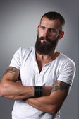 Portrait of handsome bearded man standing with crossed arms, isolated on grey background — Stock Photo