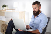 Handsome young man sitting and working on laptop computer. — Stockfoto