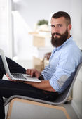 Handsome young man sitting and working on laptop computer. — Stock Photo