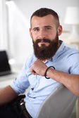 Young businessman sitting on chair in office — Stock Photo