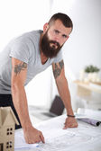 Portrait of male architect with blueprints at desk in office — Stock Photo