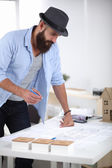 Portrait of male designer in hat with blueprints at desk — Stock Photo
