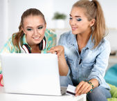 Two young women sitting with laptop  and credit cart at home — Stock Photo
