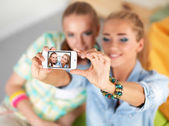 Two girls taking pictures on the phone at home — Stock Photo