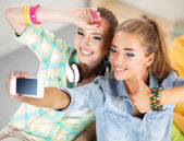 Two girls taking pictures on the phone at home and showing ok — Stockfoto