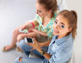 Two beautiful women sending messages with mobile, sitting — Stock Photo