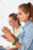 Two beautiful women sending messages with mobile, sitting — Foto de Stock