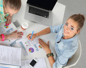 Two women working together at office, sitting on the desk — Stock Photo