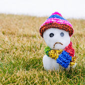 Unhappy snowman melting on green grass — Stock Photo