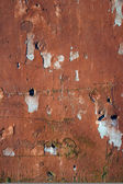 Grungy wall with peeling red paint — Stock Photo