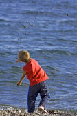 Boy throwing pebbles into the blue sea — Stock Photo